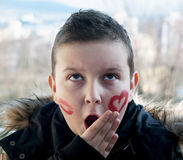 Little boy posing with painted hearts on the face Stock Photo