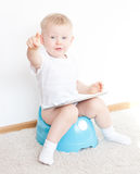 Little boy on potty with tablet pc. On the white carpet stock image