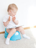 Little boy on potty with tablet pc Royalty Free Stock Photos