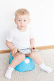 Little boy on potty with tablet pc. On the white carpet stock photography