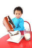Little boy pouring breakfast cereal Stock Photo