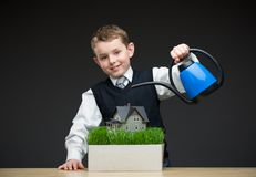 Little boy pouring home model and green grass Royalty Free Stock Photo