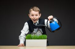 Little boy pouring house model and green grass. Portrait of little boy pouring house model and green grass with the help of water pot. Concept of investment and Stock Image