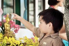 Little boy pouring water over Buddha statues Stock Photo
