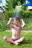 Little boy pouring water from watering can Stock Photos