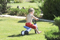 Little boy pours from a hose in the garden on a hot summer day on a green lawn, splashing water royalty free stock image