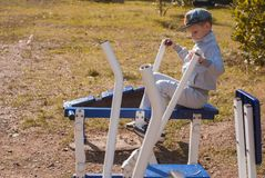 The little boy is on the power trainer on a Sunny day stock photo