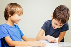 Little boy practice reading with his brother at home stock photo