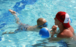 Little boy practicing kicks with swim instructor. Male swim instructor pulling little boy in the water with a buoy to practice kicking Royalty Free Stock Image