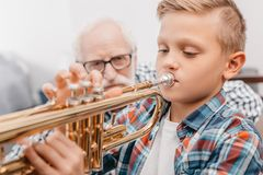 Little boy practicing playing trumpet while his grandfather royalty free stock images