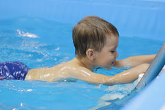 The little boy is practicing in the swimming pool royalty free stock image
