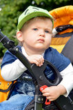The little boy in the pram. A little boy in a green hat sitting in a baby carriage Royalty Free Stock Images