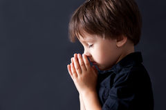 Little boy praying, child praying, isolated background Royalty Free Stock Image