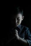 Little boy praying and praising God. Little boy praying and praising God, isolated on black Royalty Free Stock Photos