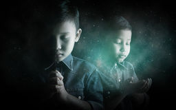Little boy praying and praising God. Little boy praying and praising God with stardust background stock images
