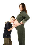 Little boy and pregnant mother. Little boy listens to hear his brother in pregnant mothers belly, isolated on white stock photo