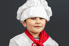 Little boy preparing healthy food on kitchen over grey backgroun Stock Images