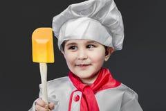 Little boy preparing healthy food on kitchen over grey backgroun Stock Photos