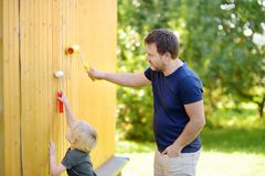 Little boy preparing to paint the wall of the house. Repair stock photography