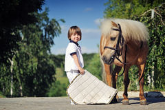 Little boy preparing to saddle up pony Royalty Free Stock Images
