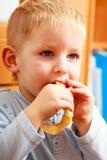Little boy preschooler eating apple peel. Stock Photos