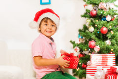 Little boy with present under New year tree Stock Photos