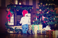 Little boy with presents looking at fireplace on Royalty Free Stock Image
