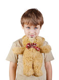 Little boy presses bear-toy by his chin to chest Royalty Free Stock Photography
