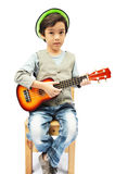 Little boy pretending  a musician with ukulele. On white background Royalty Free Stock Images