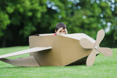 Little boy pretending to be pilot sitting in diy airplane while playing in park Royalty Free Stock Photo