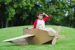 Little boy pretending to be pilot sitting in diy airplane while playing in park Royalty Free Stock Photography