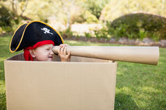 Little boy pretending to be a pirate and looking through a telescope Royalty Free Stock Images