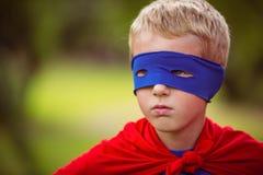Little boy pretending to be superhero. In park Royalty Free Stock Image