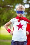 Little boy pretending to be superhero. In park Royalty Free Stock Photo