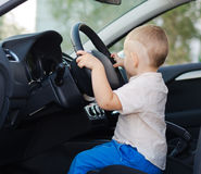 Little boy pretending to drive. Little boy sitting on the drivers seat in the car holding the steering wheel pretending to drive Royalty Free Stock Image