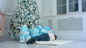 Little boy pretending to sleep on the carpet next to the Christmas tree. Professional shot on BMCC RAW with high dynamic range. You can use it e.g. in your Royalty Free Stock Images