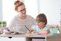 Little boy during private lesson. Education concept, smiling little boy studying with friendly young home tutor during private lesson after school Stock Photo