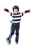 Little boy in protection helmet and in the knee and arm ruffles. Riding his scooter Stock Photos