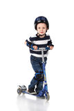 Little boy in protection helmet and in the knee and arm ruffles. Riding his scooter isolated on white background Royalty Free Stock Photography