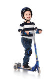 Little boy in protection helmet and in the knee and arm ruffles. Riding his scooter  on white background Stock Image
