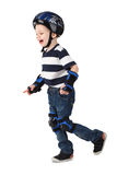 Little boy in protection helmet and in the knee and arm ruffles. Runs and laughs Isolated on white background Royalty Free Stock Photos