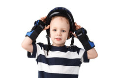 Little boy in a protective wrist pads puts or removes the protec Royalty Free Stock Image