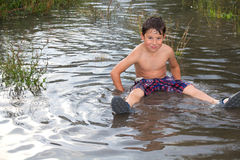 Little boy in a puddle Stock Images