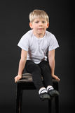 Little boy pull on hands at old stool. Little blond boy pull on his hands at old stool in black studio Stock Photo