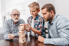 Little boy pulling a piece out of blocks wood tower while his father and grandfather. Are watching stock photo