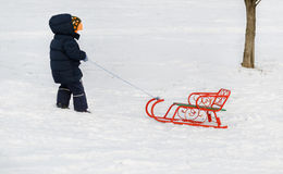 Little boy pulling a sled through winter snow Stock Photography