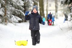 Little boy pulling yellow toboggan and holding scoop Stock Photo