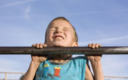 Little boy pulls on the bar. Royalty Free Stock Photo