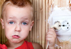 Little boy pulls the cord. From the electrical outlet stock photos