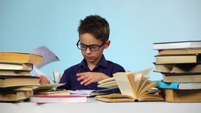 Little boy pulls out sheets of books. Blue background. Slow motion stock video footage